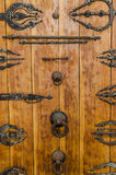 Ancient rusting wooden door with metal fittings, handles and ornaments at historic building in old town Fez, Morocco Royalty Free Stock Images
