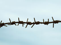 Ancient rusty barbed wire against sky Stock Photos