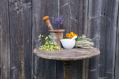 Ancient rusty iron mortar and medical herbs on old wooden table Royalty Free Stock Photos