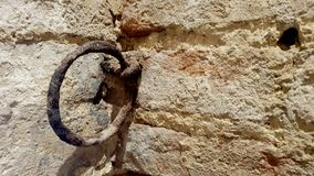 Ancient rusty wall ring. Mounted inside a medieval italian castle in the center of italy stock photography