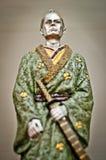 Ancient samurai statue. Samurai statue closeup. Ancient samurai statue with green kimono and katana sword Stock Photo