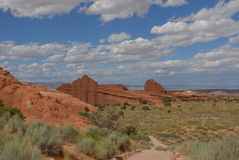 Ancient Sandstone Figurations. Arches National Park, clouds puff across landscape of red sandstone remnants of ancient sea beds Royalty Free Stock Images