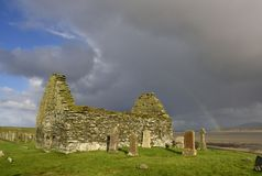 Ancient Scottish Chapel. View of the ruin of the medieval Scottish chapel and burial ground of Kilnave showing dramatic sky and rainbow over Loch Gruinart, Islay Royalty Free Stock Photos