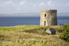 Ancient Scottish watch tower against coastline. With green, yellow grass in the foreground Stock Photos