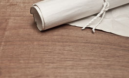 Ancient scroll with paper on wood table. Ancient scroll on wood table, closeup Stock Photo