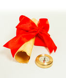Ancient scroll tied up by red ribbon and compass. On light background Royalty Free Stock Images
