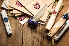 Ancient scrolls and old envelope with blue inkwell. On old wooden table Stock Photos