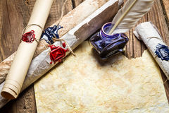 Ancient scrolls written with ink and feather bird. On old wooden table Stock Photo