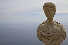 Ancient sculpture high above the sea Stock Images