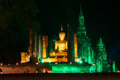 Ancient sculpture of a seated Buddha on the ruins of the Buddhist temple Wat Mahathat in the yellow-green night illumination. Sukh. Othai. Thailand Stock Image