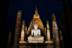 Ancient sculpture of a seated Buddha in the ruins of a Buddhist temple Wat Sa Si on the night. Sukhothai Park, Thailand. Ancient sculpture of a seated Buddha in Royalty Free Stock Images