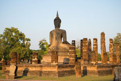 Ancient sculpture of a seated Buddha at the ruins of the temple Wat Chana Songkhram in the rays of the setting sun. The view from Stock Images