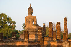 Ancient sculpture of a seated Buddha on the ruins of the temple Wat Chana Songkhram. The view from the back. Sukhothai, Thailand Royalty Free Stock Images