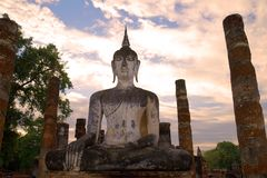 Ancient sculpture of the sitting Buddha close up at sunset. Historical park of the Sukhothai city, Thailand. Ancient sculpture of the sitting Buddha close up at stock photo