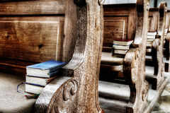 Ancient seats. Wooden seats in an antique church with books on it Royalty Free Stock Images