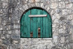 Ancient semicircular window with nailed green wooden shutters. Stock Images