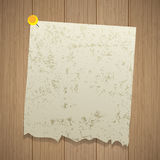 Ancient sheet of torn paper pinned with a pin. Wooden background. Ancient  sheet of torn paper pinned with a pin. Wooden background Stock Photo