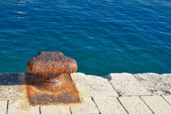 Rusty iron bollard by the sea Royalty Free Stock Image