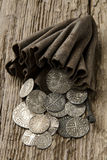 Ancient silver coins in purse. Ancient hammered silver coins over 500 years old spilling out of an ancient purse Royalty Free Stock Photo