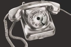 An ancient silver dial disk phone in futuristic processing on isolated black background.  stock image