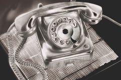 An ancient silver dial disk phone in futuristic processing on on the table on a stand dark background. An ancient silver dial disk phone in futuristic processing royalty free stock photo