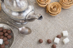 Ancient silver teapot. Sugar cubes and chocolate dragees on canvas Royalty Free Stock Image