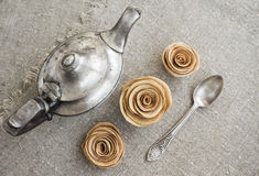Ancient silver teapot. Sugar cubes and chocolate dragees on canvas Stock Photos