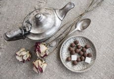 Ancient silver teapot. Sugar cubes and chocolate dragees on canvas Stock Photography