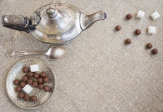 Ancient silver teapot. Sugar cubes and chocolate dragees on canvas Stock Photo