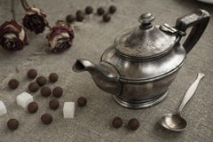 Ancient silver teapot. Sugar cubes and chocolate dragees on canvas Stock Images