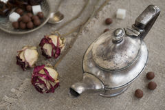 Ancient silver teapot. Sugar cubes and chocolate dragees on canvas Royalty Free Stock Images