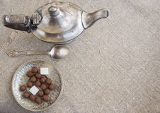Ancient silver teapot. Sugar cubes and chocolate dragees on canvas Stock Image