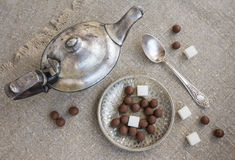 Ancient silver teapot. Sugar cubes and chocolate dragees on canvas Royalty Free Stock Photos