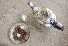 Ancient silver teapot. Sugar cubes and chocolate dragees on canvas Royalty Free Stock Photography