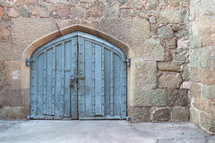 Ancient single wooden castle door in old city wall. Arched medieval wooden door in a stone wall. Royalty Free Stock Photos