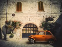 Ancient small orange Italian car, parked on the road in front of an ancient dwelling.