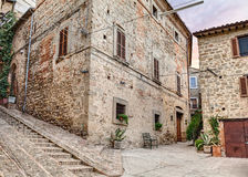 Ancient small square in Italy. Picturesque ancient corner, narrow alley and stairway in medieval town Gualdo Cattaneo, Umbria , Italy Royalty Free Stock Images