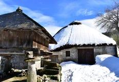 Ancient snowy palloza house and wooden horreo granary galician granary. Piornedo, Ancares, Galicia, Spain. royalty free stock photography