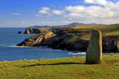 Ancient Standing stone above rugged and wild coastline. Standing stone above rugged and wild Pembrokeshire coastline at Trefin, Pembroke. The three headlands you stock image