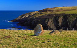 Ancient Standing stone above rugged and wild Pembroke coastline Royalty Free Stock Photos