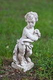 Ancient statue of child and grass background Royalty Free Stock Image