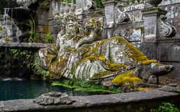 Ancient statue covered with moss royalty free stock image