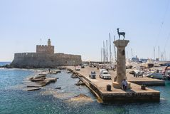 Ancient statue of a deer and a medieval lighthouse Rhodes Stock Photo