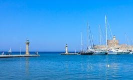 Ancient statue of a deer and a medieval lighthouse. Rhodes Stock Image