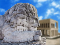 Ancient statue of a lion  isolated on old village background Stock Images