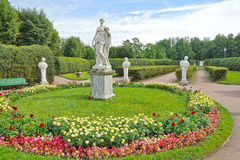 Ancient statues in the flower garden Stock Photo