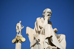Socrates & Apollo. Statues of ancient philosopher Socrates and ancient god Apollo at the background, Athens - Greece Stock Image