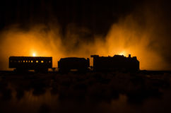 Ancient steam locomotive in night. Night train moving on railroad. orange fire background. Horror mystical scene. Train moving in fog. Ancient steam locomotive Stock Image