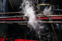 Ancient steam locomotive in steam. Live steam around mechanical Royalty Free Stock Image