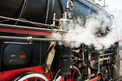Ancient steam locomotive in steam. Live steam around mechanical Stock Photo